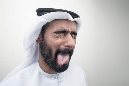 disdain: arabian man sticking out his tongue, Arabian guy with funny expression? Stock Photo