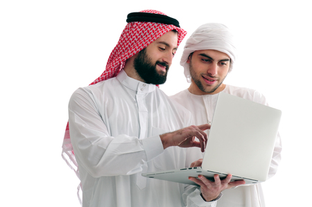 Two Arabian Businessmen Analyzing results holding a laptop over a white background, business concept