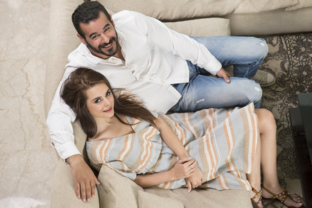 Top view of a beautiful Young Couple Sitting on a Couch, Couple in love sitting in a modern interior Stock Photo
