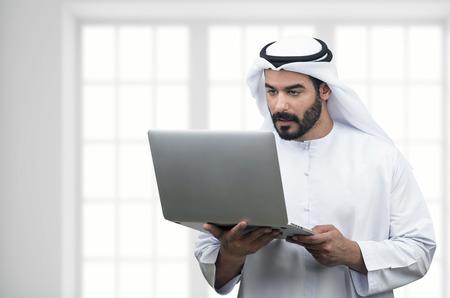 KSA: Arabian Business man using notebook in a modern office