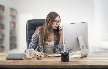 Busy Businesswoman in office and talking on mobile phone