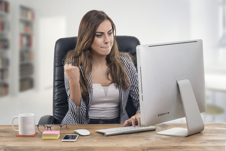 Young attractive businesswoman expressing success at office