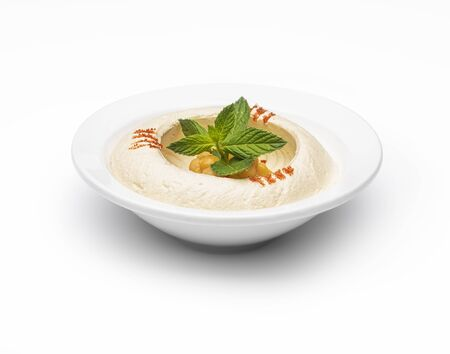Arabic food Hummus with mint in a bowl isolated on white