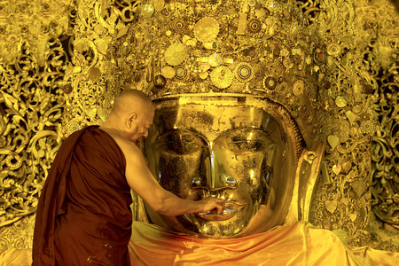 MANDALAY-JAN 25 The senior monk put wax on Buddha image lips  in ritual of face wash to Mahamuni Buddha image on JAN 25,2013 at Mahamuni temple-Mandalay Myanmar