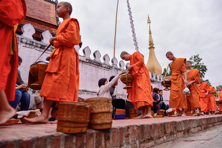 Luang Pra bang, Laos : 13 DEC 2014 Unidentified monks walk to collect alms and offerings.This procession is held every early morning in Luang prabang.