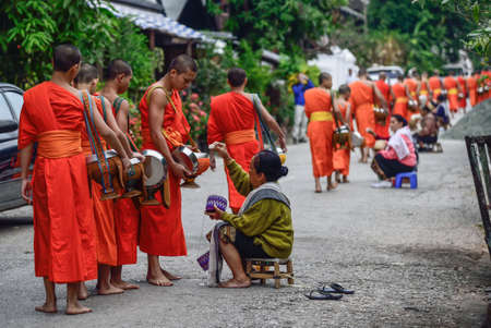 alms: Luang Pra bang, Laos : 13 DEC 2014 Unidentified monks walk to collect alms and offerings.This procession is held every early morning in Luang prabang.
