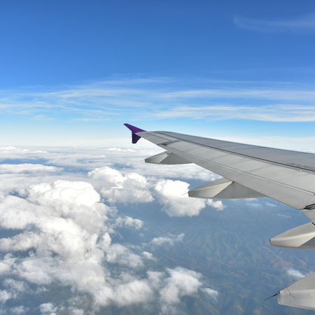 air transport: Plane window with blue sky and clouds outside
