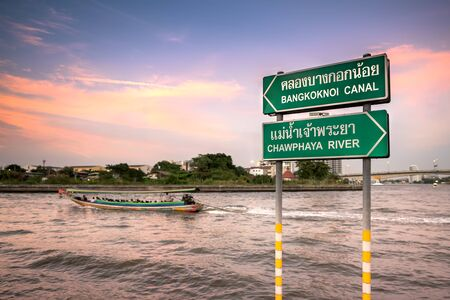 Long-tail boats on the Chao Phraya river and Bangkoknoi canal at sunset. Image with selective focus and toning Stock Photo