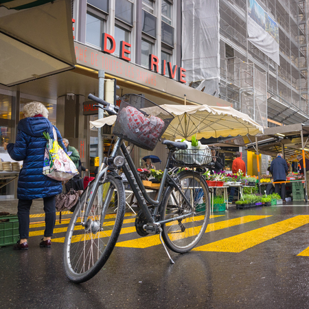 go to the shopping: Geneva, Switzerland - April 16, 2016 : People park the bicycle while they go shopping at street market in Geneve, Switzerland Editorial