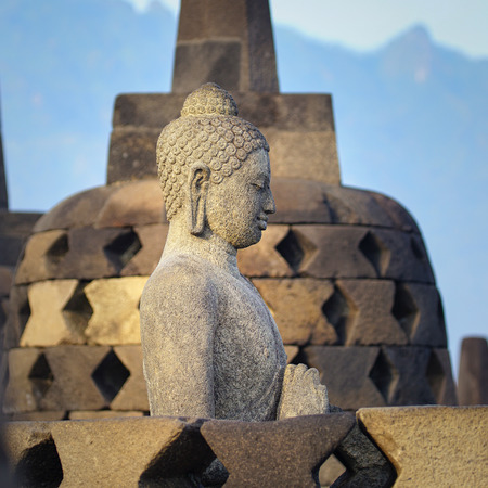 Carved stone buddha statue in small stupa around top of Borobudor, world largest buddhist temple in Yogyakarta, Indonesia.