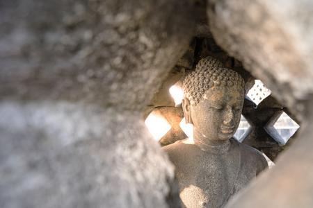 Carved stone buddha statue inside small stupa around top of Borobudor, world largest buddhist temple in Yogyakarta, Indonesia.