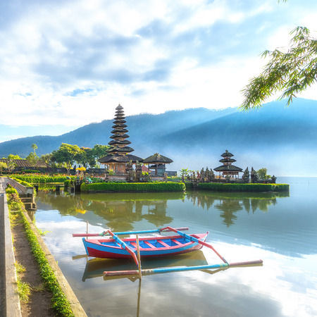 bratan: Pura Ulun Danu Bratan, floating temple with local boat in fore ground, Famous Hindu temple on Bratan lake in Bali, Indonesia.Image with soft focus in background.