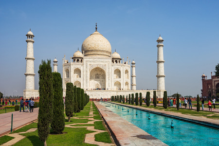 front elevation of Taj Mahal with fountain pond in foreground in a sunny day.