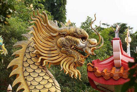 path to wealth: golden dragon statue on the roof of chinese temple Stock Photo
