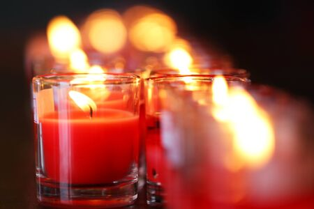 Row of close-up Red prayer candles in small glasses in catholic church