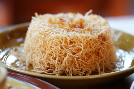 crispy Thai rice noodles with Sweet and Sour sauce in brown ceramic plate, Thai people called Mee Krob