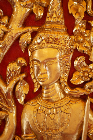 close-up male Thai angel statue filled with gold leaf isolated with red backgrounds, wooden crafting product painted with gold colors, guardian traditional souvenir
