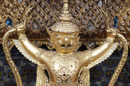 close up golden Garuda statue stand around , the bronze symbol of Thai government, giant ancient gold eagle with crown sculpture antique signature on temple royal palace wall, travel destination backgrounds Stock Photo