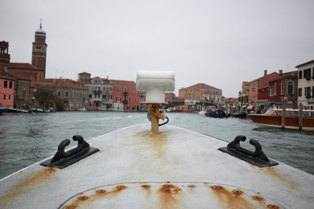 First person view of ancient rusty metal boat with old italian venice city and river scape cloudy Sky, perspective exploring the ocean, traditional grand canal boat trip in Venezia, commercial advertisement
