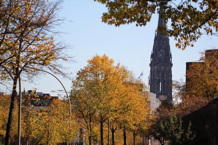 Autumn park St. Nicholas Church, attractive ruined landmark at Hamburg Germany, St. Nikolai Kirche's charred remains, commercial advertisement backgrounds