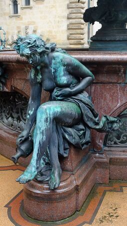 Sitting antique metal green statue of young naked woman, Venus sculpture, decorating art fountain backgrounds