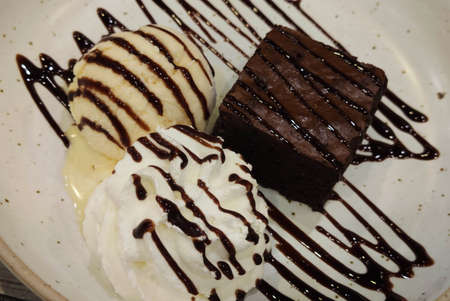 Close-up shaped Chocolate lava cake with syrup and Vanilla sweet Ice Cream decorated with dark cholocate sauce on white ceramic plate at fusion gourmet cafe restaurant, food stylist backgrounds 写真素材