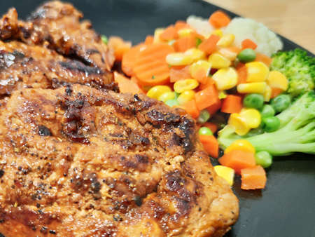 Sliced Grilled organic pork, beef Ribeye steak decorated with various colorful vegetables dressing corn carrot peas lemon serving on white plate on wooden table, One famous menu of secret recipe from