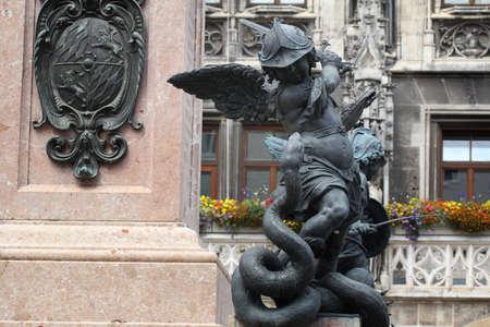 Close-up ancient statue of Putto killing devil at the Marian column's pedestal Marienplatz, Munich, Germany, travel destination backgrounds