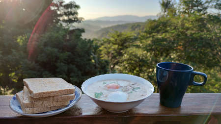 rice porridge with pork and boiled egg with coriander leaf on white bowl serving with black mug of home made coffee and grilled Whole wheat bread in the middle of forest mountain in Summer season, adv