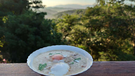 rice porridge, rice gruel with pork chicken frake and boiled egg with coriander leaf serving on white bowl in the middle of forest mountain in Summer season, advertisement home stay backgrounds