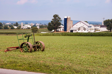 Amish Farm on Sunny Cloudless Summer Day, with Barn, Silos, and Farm House and Old Farm Equipment