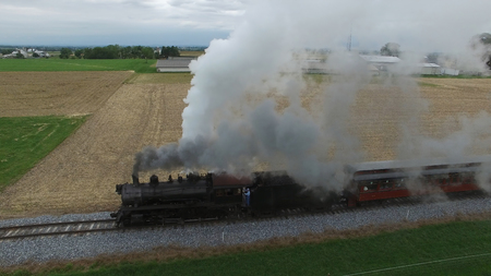 Aerial View of a Steam Passenger Train Puffing Smoke in Amish Countryside on a Sunny Spring Day Imagens
