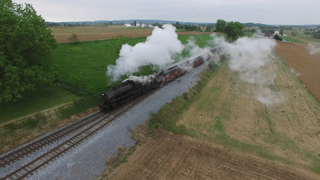 Aerial View of a Steam Passenger Train Puffing Smoke in Amish Countryside on a Sunny Spring Day Banco de Imagens