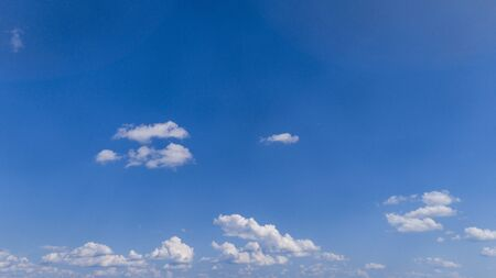 White Fluffy Clouds Floating in the Bright Blue Skies on a Summer Day