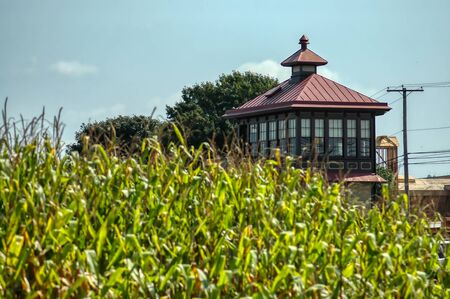 Train Station Switch Tower Seen Thru Corn Field on a Sunny Summer Day Stock Photo