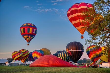 Hot Air Balloon Festival Morning, Sunrise Launch of Multiple Balloons on a Sunny summer Morning Archivio Fotografico