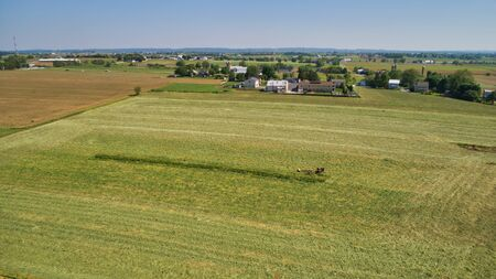 Aerial View of an Amish Farm Harvesting his Crop using Horses and Antique Equipment as Seen by a Drone