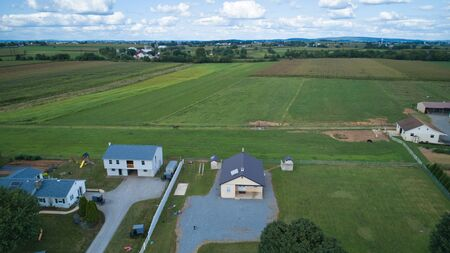 Aerial view of Amish countryside with barns and silos and a one room school house on a sunny summer day 스톡 콘텐츠