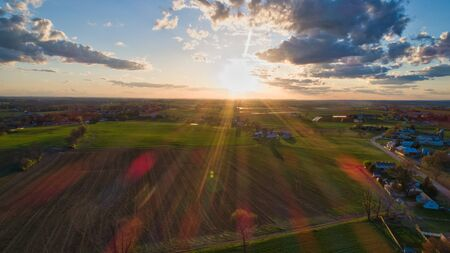Aerial view of a Sunset over barns, silos and farmlands during the golden hour with blue sky, clouds and red sun 스톡 콘텐츠 - 147957350