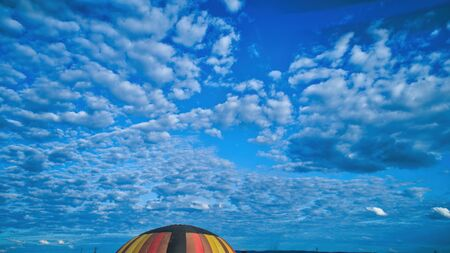 Aerial view of blue sky and multiple clouds and a hot air balloon floating thru it