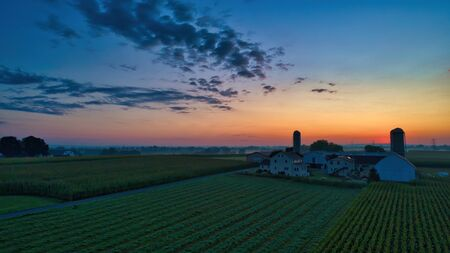 Sunrise over barns, silos and green farmlands with blue, red and orange skies and a few clouds with a mist on the ground 스톡 콘텐츠 - 147957381