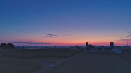 Sunrise over barns, silos and green farmlands with blue, red and orange skies and a few clouds with a mist on the ground
