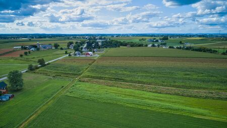 Aerial view of Amish countryside with barns and silos on a sunny summer day