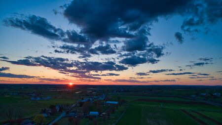 Aerial view of a Sunset over barns, silos and farmlands during the golden hour with blue sky, clouds and red sun 스톡 콘텐츠 - 147957388