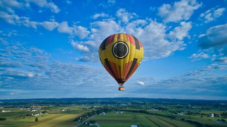 Aerial view of blue sky and multiple clouds and a hot air balloon floating thru it 스톡 콘텐츠 - 147957392