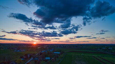Aerial view of a Sunset over barns, silos and farmlands during the golden hour with blue sky, clouds and red sun