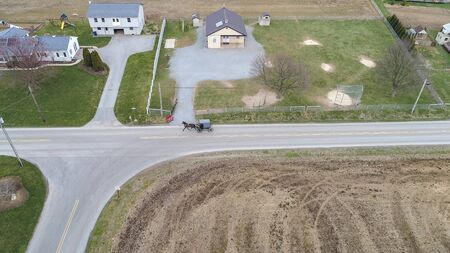 Aerial of an Amish horse and buggy riding on a road on a spring day 스톡 콘텐츠 - 147957394