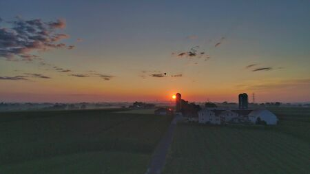 Sunrise over barns, silos and green farmlands with blue, red and orange skies and a few clouds and a hot air balloon in the distance with a mist on the ground
