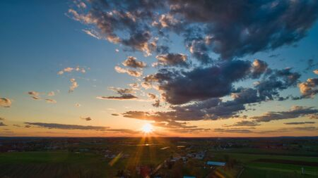 Aerial view of a Sunset over barns, silos and farmlands during the golden hour with blue sky, clouds and red sun 스톡 콘텐츠 - 147957416