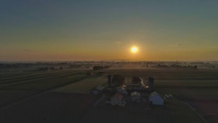 Sunrise over barns, silos and green farmlands with blue, red and orange skies and a few clouds with a mist on the ground 스톡 콘텐츠 - 147957419
